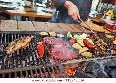 chef grilling meat, fish and vegetables on flame in restaurant kitchen