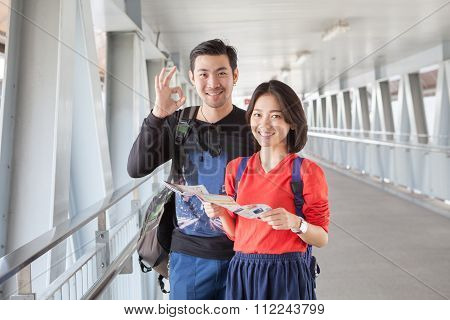 Younger Asian Traveling Man And Woman Standing With Toothy Smiling Face Sigh All Right By Okay Hand
