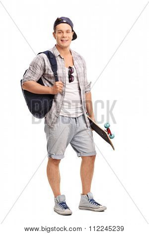 Full length portrait of a young skater holding a skateboard and carrying a blue backpack isolated on white background