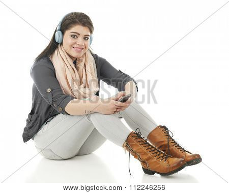An attractive teen girl happily sitting on the floor listening to her cell phone with headphones.  On a white background.