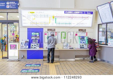 Passengers are buying tickets from vending machines inside JR Kyoto Station