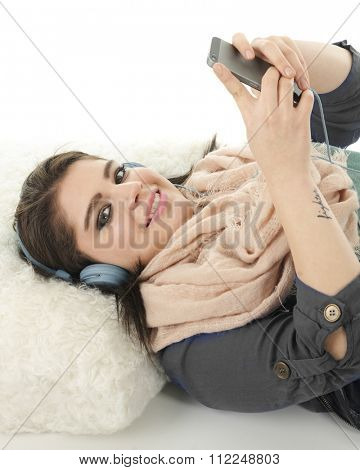 A beautiful teen girl laying on a pillow listening to her cell phone with headphones.  On a white background.