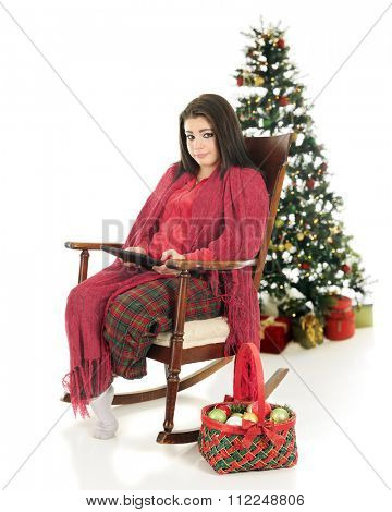 A beautiful teen girl snuggled up in her pajamas and a blanket while working on her ipad.  A basketful of ornaments are nearby with a decorated tree behind her.  On a white background.
