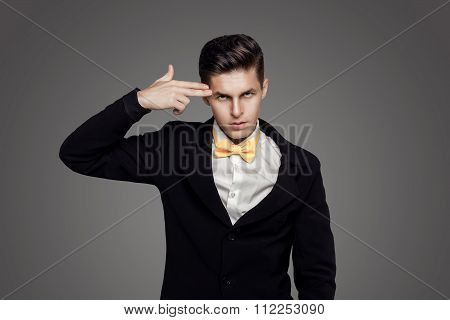 Portrait Of Young Trendy Groom With Yellow Bow-tie With Gun Sign