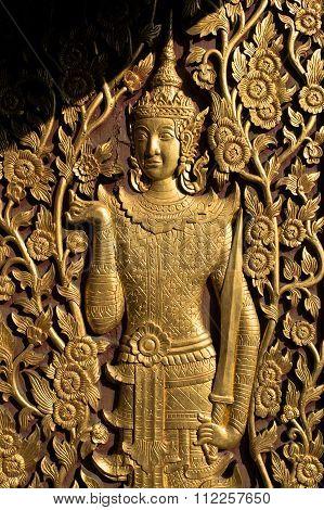 Gold deity hold sword sculptured wood door in temple , thailand
