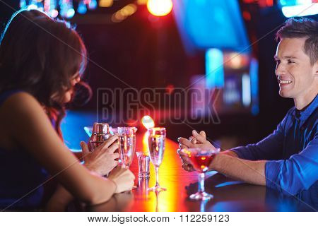 Happy young man talking to girl while having drink in night club