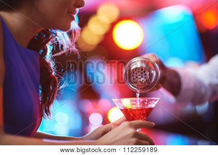 Girl holding martini glass while barman pouring cocktail