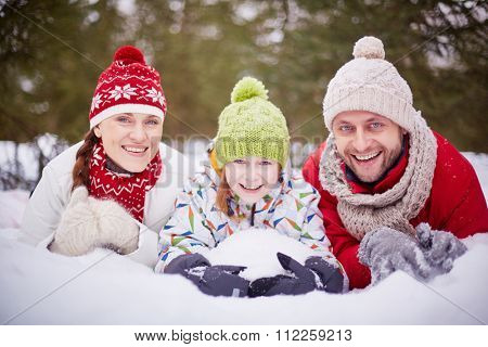 Joyful family lying in snowdrift and looking at camera with smiles