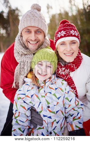 Happy family in winter-wear looking at camera