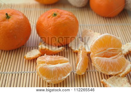 Ripe Mandarin fruit peeled open and place on woodwn table with group of mandarin fruits and leaves o