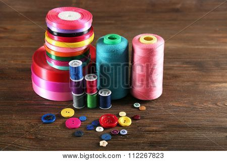 Spools of color ribbon, thread and buttons on wooden background