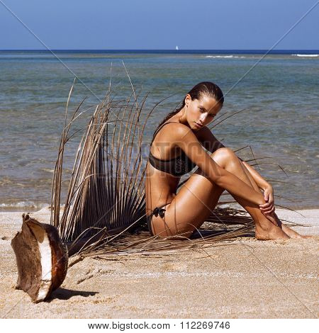Woman in bikini with palm branch on beach near sea enjoying sun. Long wet hair. Volume curly hairsty