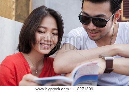 Couples Of Asian Younger Traveling Man And Woman Reading A Guide Book With Happiness Face Toothy