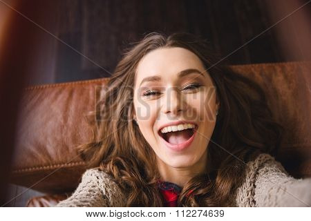 Portrait of a cheerful woman lying on the sofa and making selfie photo