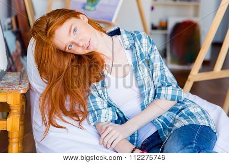 Relaxed pensive young female with long red hair lying on white beanbag in art studio