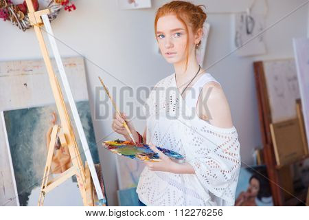 Thoughtful attractive young female painter using oil paints for painting on canvas in art workshop