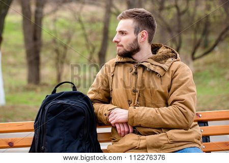 Portrait of a pensive man sitting on the bench outdoors