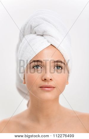 Portrait of beautiful natural young woman with white towel on her head over white background