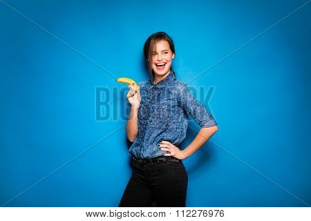 Woman With Banana In Hands On Blue Background