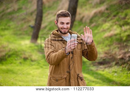 Portrait of a smiling man doing video call outdoors on smartphone