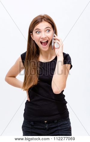 Cheerful excited young woman talking on cell phone over white background