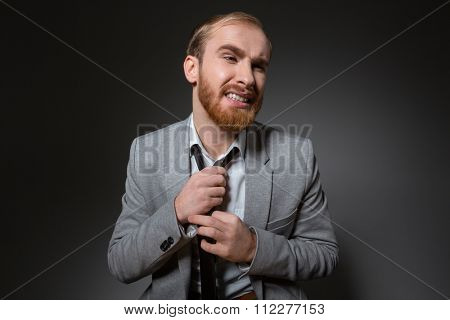 Annoyed bearded businessman in grey suit taking off his tie over grey background