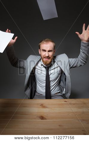 Aggressive wicked bearded businessman in grey jacket and tie sitting at the table and throwing documents around over grey background