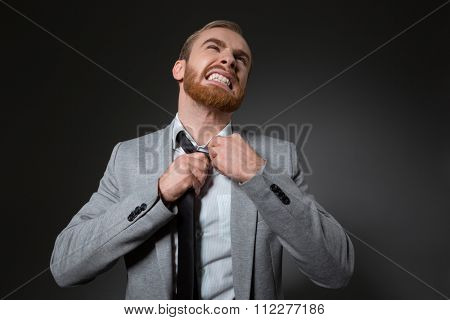 Irritated angry business man in grey jacket mad because of his tie over grey background