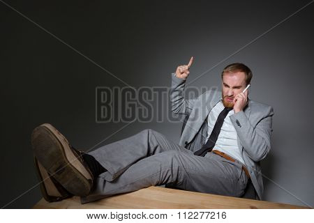 Irritated rage bearded businessman talking on cell phone and yelling over grey background
