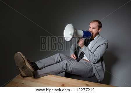 Mad annoyed businessman in grey suit sitting and shouting in megaphone over grey background