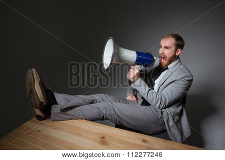 Angry crazy bearded bisnessman sitting with legs on table and shouting in loudspeaker over grey background
