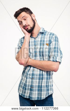 Portrait of sleepy tired handsome young man with beard in plaid shirt standing over white background