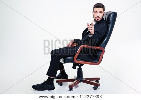 Thoughtful handsome young business man with beard in black suit in black office chair pointing on you over white background