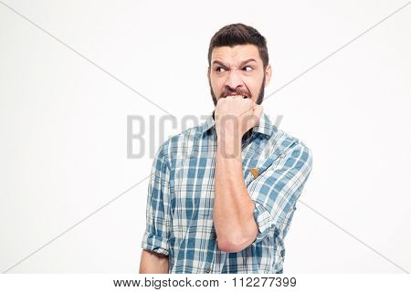 Angry irritated aggressive young bearded man in plaid shirt biting his fist over white background