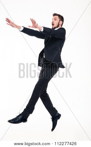 Stunned afraid young bearded businessman in black suit flying with strong wind blowing on him over white background