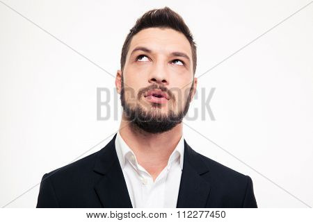 Portrait of pensive attractive bearded young man in formalwear thinking and looking up over white background