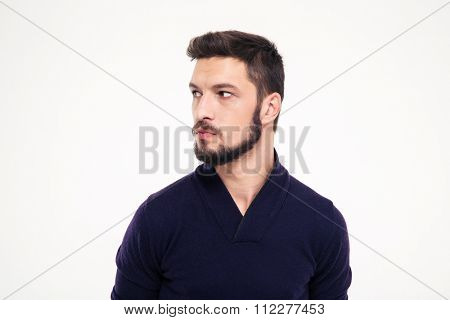 Potrait of attractive thoughtful young man with beard in sweetshirt looking away over white background