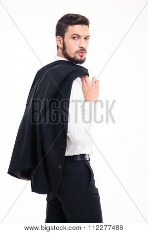 Handsome confident young businessman with beard in black siut and white shirt holding jacket on shoulder over white background