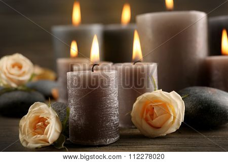 Alight wax grey candles with roses on wooden background