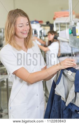 woman putting a jacket on a hanger