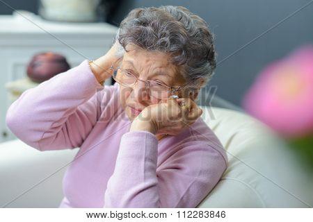 Elderly lady holding her head in her hands
