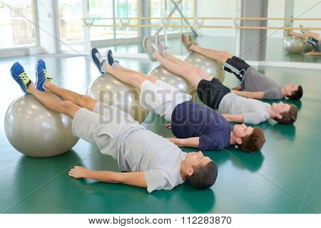 Four men exercising with aerobic balls