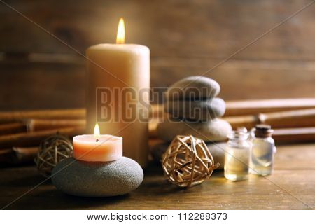 Decorated composition with candles, pebbles and bamboo on wooden background
