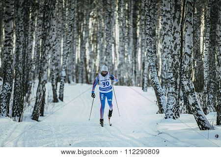 young girl athlete skier rides on track in birch forest classic style