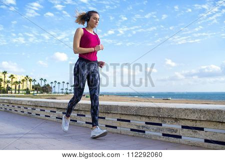 Young Blonde Sportswoman Running On Shoreline