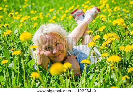 A Woman Lies In A Clearing And Sniffs A Flower