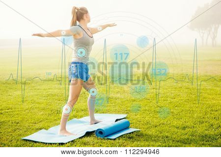 Sporty blonde doing yoga on exercise mat against heart rate monitor