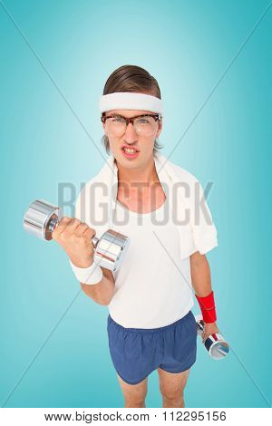 Geeky hipster lifting dumbbells in sportswear against blue vignette background