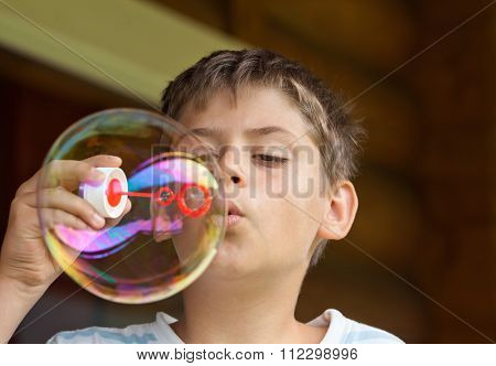 Boy Blowing Soap Bubble