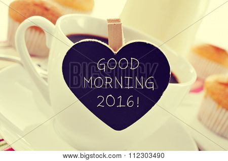 closeup of a porcelain cup of coffee with a heart-shaped signboard with the text good morning 2016 on a set table for breakfast
